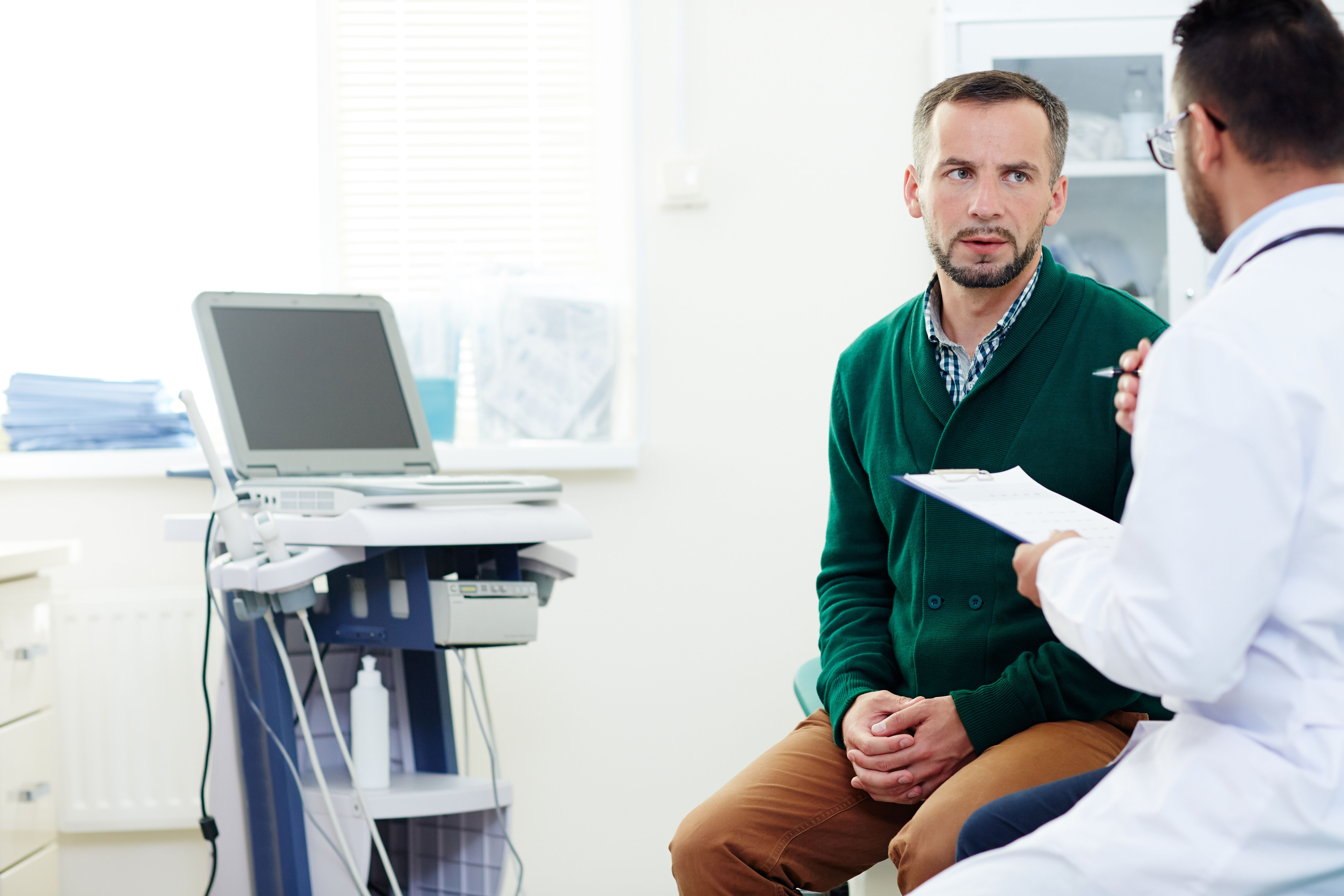 Serious patient listening to advice of professional practitioner after examination